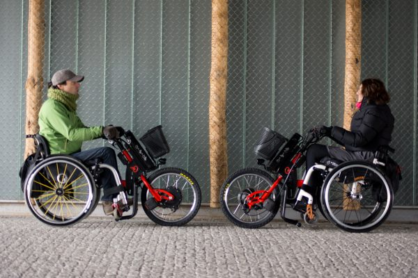 Two people in wheelchairs with Batec Electric attachments riding outside