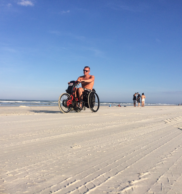 Alex rides his Batec Electric along a beach in Florida