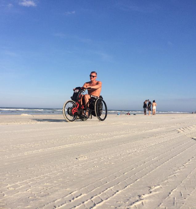 Alex rides his Batec Electric along a beach in Florida